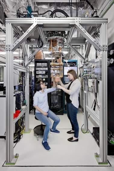 Naukowcy zajmujący się komputerami kwantowymi, Hanhee Paik (z lewej) oraz Sarah Sheldon (z prawej), sprawdzający system kwantowy IBM Q przed włożeniem do komory chłodniczej. Zdjęcie wykonano w laboratorium IBM Q Lab, w należącym do firmy IBM ośrodku T. J. Watson Research Center w Yorktown.